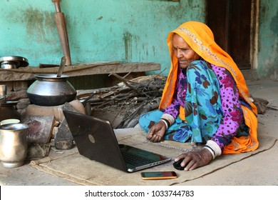 Old Indian traditional  lady amazed using Laptop. Indian grandma using laptop and internet for first time. Excited and Curious. Indian open Kitchen in background.