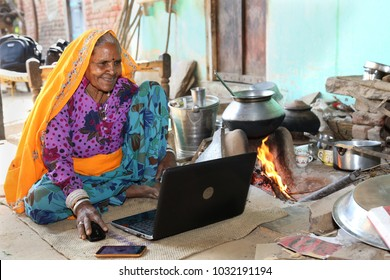 Old Indian traditional  lady smiling using Laptop. Indian grandma happy to use laptop and internet for first time. She loves technology, Happiness of Knowledge. Excitement of first use of Laptop.