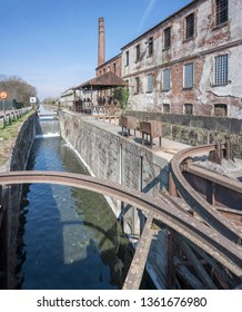 old industrial buildings and millwork of lock on Naviglio canal, shot in bright spring light at Rozzano, Milan, Lombardy, Italy
