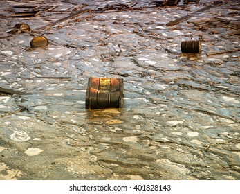 Old industrial metal barrels surrounded by contaminated environment.
