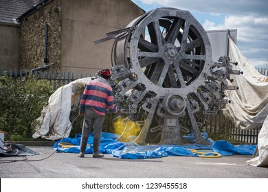 An old industrial steel and iron wallpaper manufacturing rolling machine being spray painted outdoors yellow by a man. Old industrial british engineering being restored to former glory.