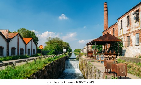 Old industrial warehouses alongside a cascade on a lock at the Naviglio Pavese, a canal that connects the city of Milan with Pavia, Italy