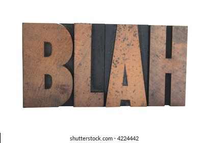 old, ink-stained wood letterpress type spells out the word 'BLAH' isolated on white