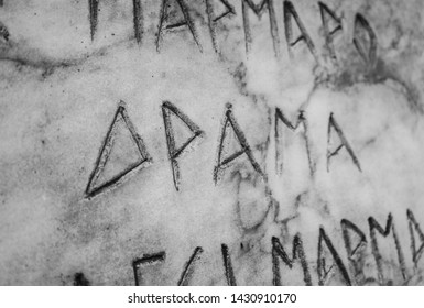 Old inscription on marble, Greek letters engraved, drama sign.