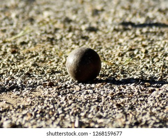 Old iron boules in a gravel field, for students to practice in boules courses.