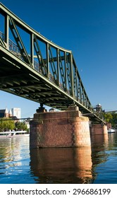 Old iron bridge in Frankfurt germany with brick pylons