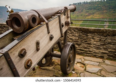 Old iron cannon on an outpost. Old iron war weapon with rusty texture.
