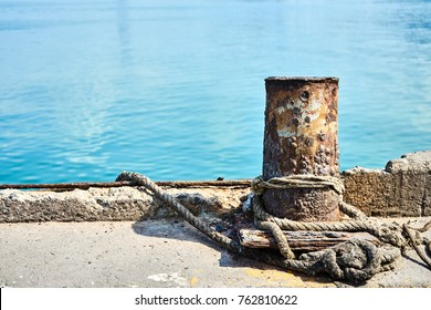 Old iron dock cleat in dock. Old mooring bollards with rope