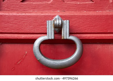 Old iron door knock, painted with gray rust protection paint, fastened to a red wood door.