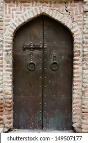 Old iron door in the red brick wall in Old Tbilisi, Georgia