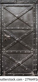 Old iron door reinforced with steel belts and rivets