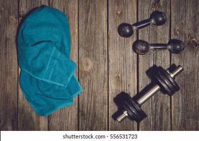 Old iron dumbbells or exercise weights outdoor on an old wooden deck, floor or table in the gym. Image frame taken from above, top view. A lot of copy space around product