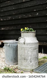 Old iron Dutch milk can and a iron waste bin together against a black wooden plank wall