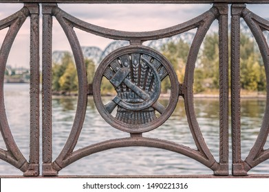 old iron fence on the waterfront with a medallion in the form of a hammer and sickle against wheat ears