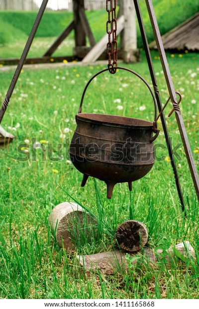 An old iron kettle suspended over some dry logs for cooking.