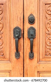 old iron lock on the wooden carved pattern door