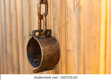 old iron shackles hanging on chains on wooden background, handcuffed traditional captivity of slaves