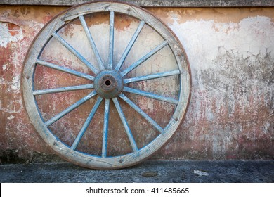 Old ironed, blue wagon or carriage wheel on old wall with peeling paint