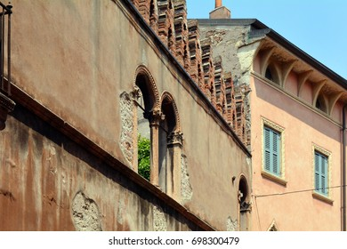 Old Italian buildings with red brick wall and arches on columns