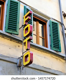 Old italian commercial business foto sign on a building with a green shuttered window in the background