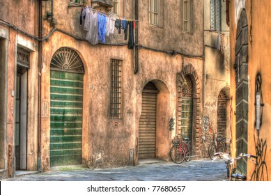 An old Italian lane with washing hanging on the line and bycicles resting in Tuscany Italy
