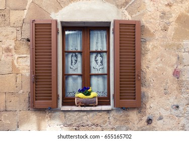 old italian window with the flowers on a window sill