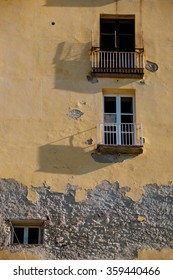 Old Italian yellow stone house front with balcony and window