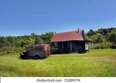 Old jalopy sits in yard of abandoned log cabin in the Ozark Mountains of Arkansas.  Cabin has tin roof and old truck has faded sign saying hillbilly.