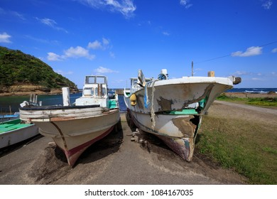 Old Japanese fishing boats sit dockside in a state of disrepair