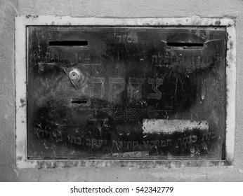 old jewish charity box into a wall with the word charity in hebrew, in black and white