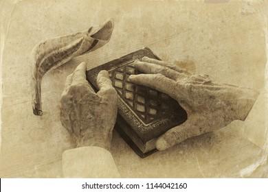 Old Jewish man hands holding a Prayer book, praying, next to shofar (horn). Jewish traditional symbols. Rosh hashanah (jewish New Year holiday) and Yom kippur concept