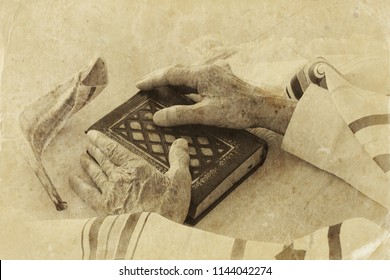 Old Jewish man hands holding a Prayer book, praying, next to tallit and shofar (horn). Jewish traditional symbols. Rosh hashanah (jewish New Year holiday) and Yom kippur concept