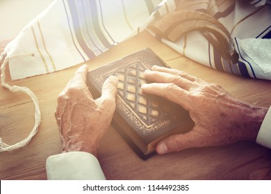 Old Jewish man hands holding a Prayer book, praying, next to tallit and shofar (horn). Jewish traditional symbols. Rosh hashanah (jewish New Year holiday) and Yom kippur concept