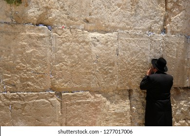 Old Jewish rabbi otrodoks recites a prayer in front of the western wall in the old city of jerusalem in israel