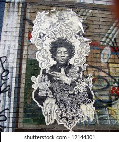 old Jimi Hendrix poster on a building with graffiti