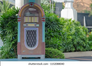 Old jukebox stands among green bushes