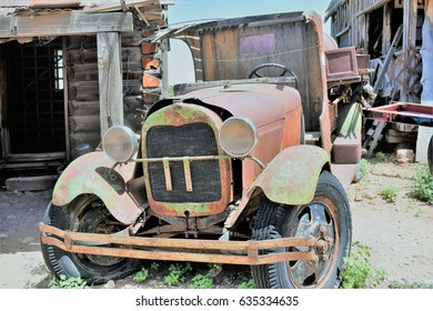 Old junker truck sits in dirt near deserted gray wood  structures at a ghost town on the outskirts of Jerome, Arizona