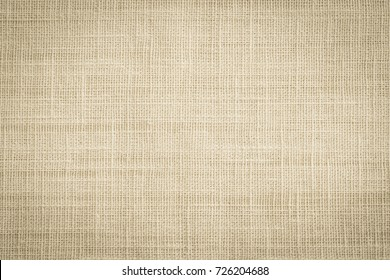 Old jute hessian sackcloth canvas sack cloth woven texture pattern background in aged yellow beige cream brown color