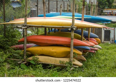 Old kayaks and canoes lie on the open-air rack. yellow orange blue red plastic boats
