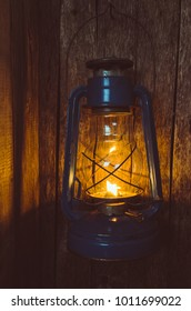 Old kerosene lamp illuminates the old wooden wall