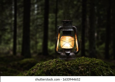 Old kerosene lamp on the moss in mysterious dark forest. Vintage lantern lighting. Copy space.