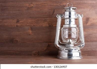 Old kerosene lantern on the dark wooden background