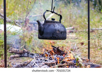 An old kettle over the camp fire. The kettle boils water for tea.