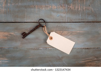 old key with empty tag on wooden background