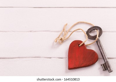Old  key with a heart on white wooden background