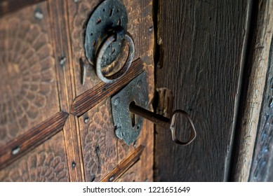 Old key in the keyhole on a old wooden church door. Close up shot.