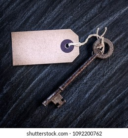 Old Key and Vintage Brown Luggage Label on a dark background.