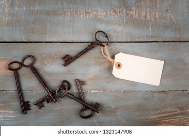 old keys with empty tag on wooden background