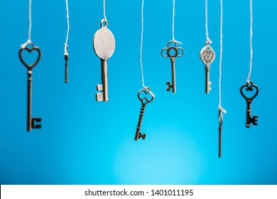 Old Keys Hanging With Strings In A Row Against Blue Backdrop