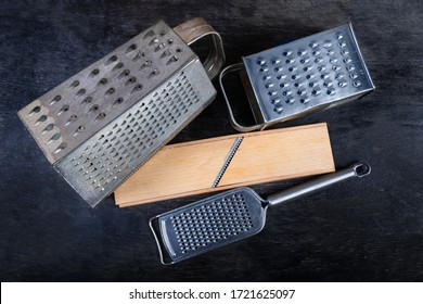 Old kitchen box graters with multiple grating surfaces and different holes, flat grater and wooden grater with special stainless steel blade on the black surface